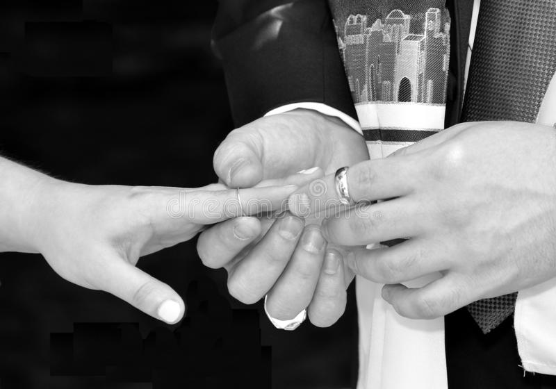 Timeless Moment. When the groom slips the wedding band onto the brides finger to consummate the wedding bond of marriage. Photo is in black and white stock photos
