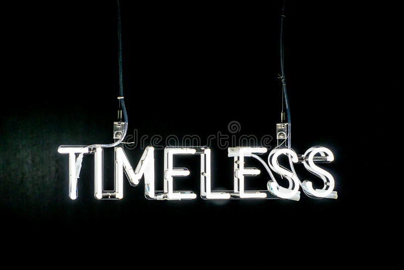 Timeless neon sign. Illuminated white Timeless neon sign on a dark black background with copy space above royalty free stock photo
