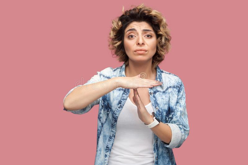 Timeout. I need more time. Portrait of worry pleased young woman with curly hairstyle in casual blue shirt standing with T gesture stock photo
