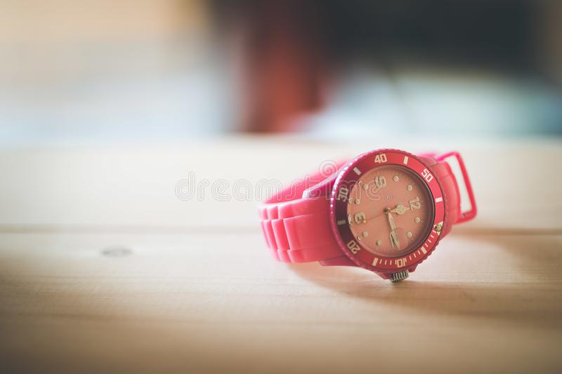 Times goes by, pink watch on a wood shelf. Whristwatch ticker home age hip modern text space pop art colourful timer minute lifestyle display closeup hours royalty free stock photography