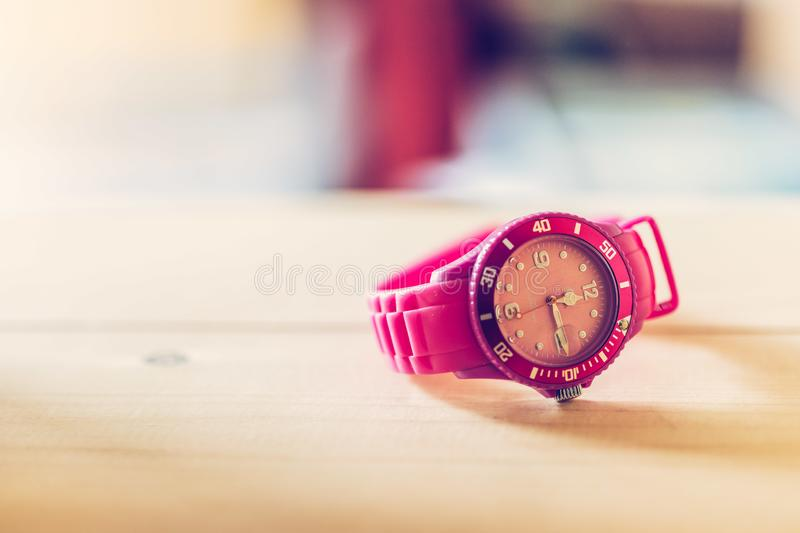 Times goes by, pink watch on a wood shelf. Whristwatch ticker home age hip modern text space pop art colourful timer minute lifestyle display closeup hours royalty free stock photos