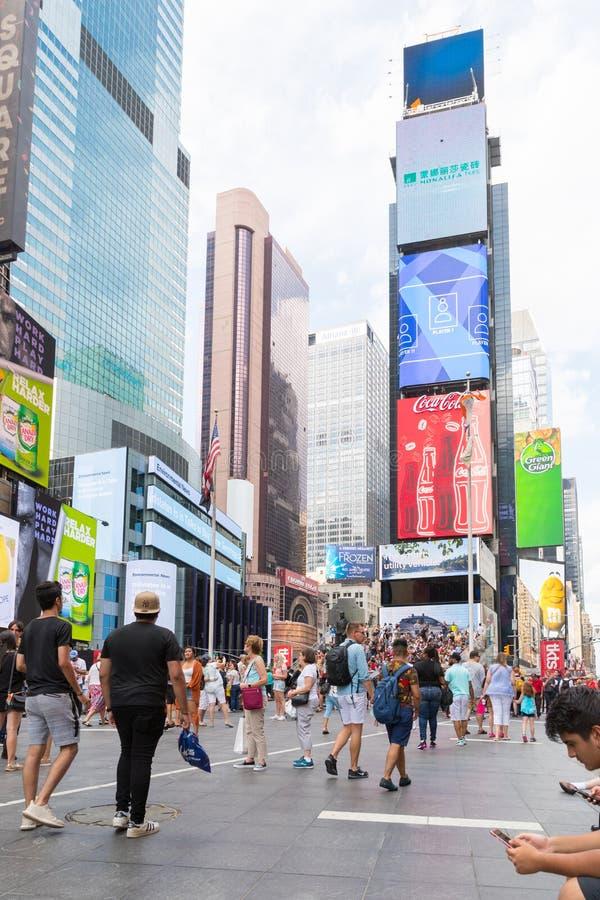 Times Square är en upptagen turist- genomskärning av den neonkonst och komrets och är en iconic gata av New York City arkivfoton