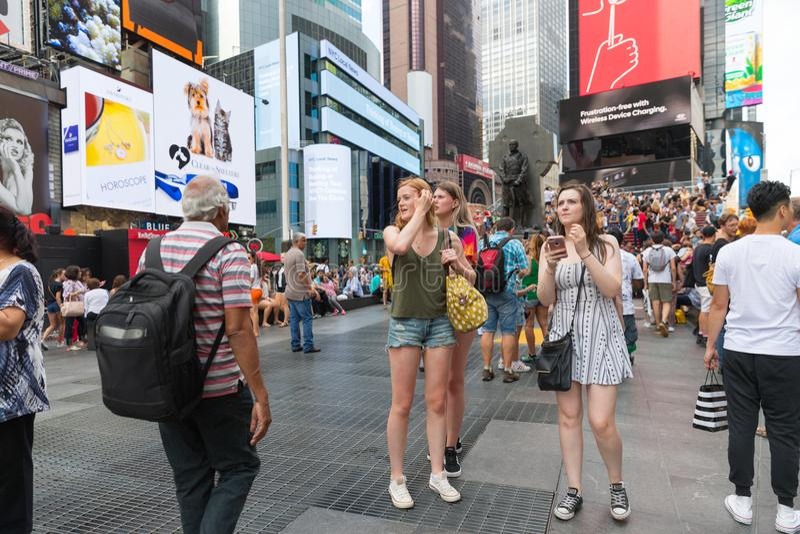 Times Square är en upptagen turist- genomskärning av den neonkonst och komrets och är en iconic gata av New York City arkivbilder