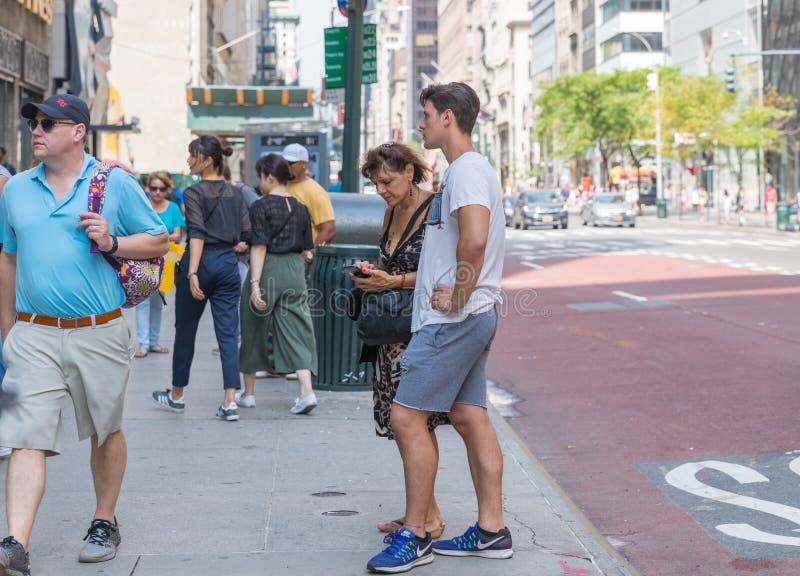 Times Square är en upptagen turist- genomskärning av den neonkonst och komrets och är en iconic gata av New York City och Amerika arkivbilder