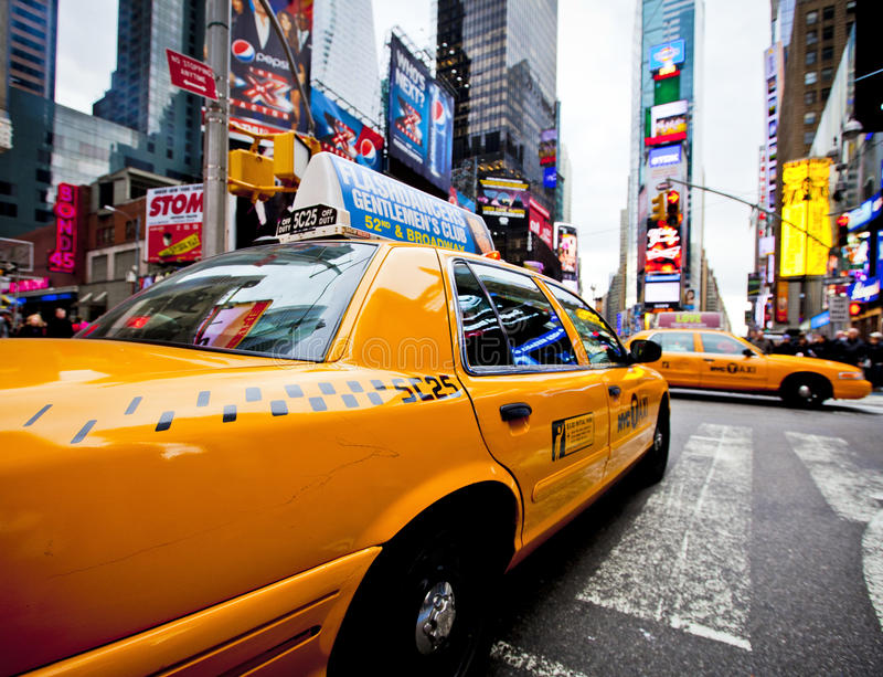 Times Square. NEW YORK - DECEMBER 17: Yellow cab speeds through Times Square the busy tourist intersection of neon art and commerce and is an iconic street of