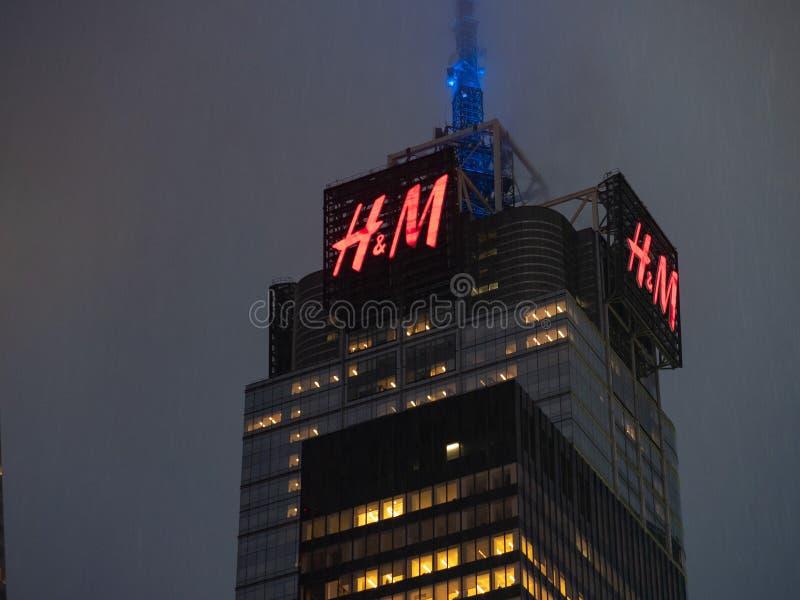 4 Times Square che costruiscono con il segno di H&M che tesse su su una d piovosa immagine stock