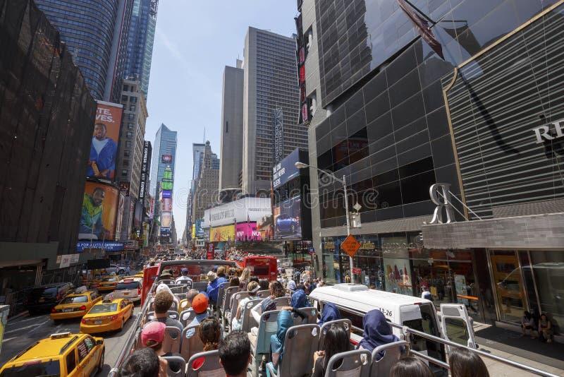 Times Square con los turistas en autobús imagenes de archivo