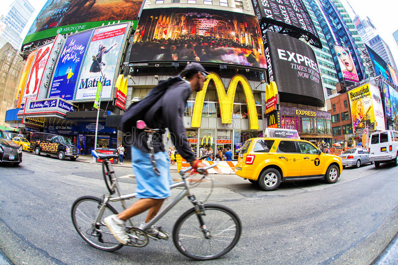 Times Square with cyclist,New York City. Bicycles in traffic along Times Square in New York City, New York, USA on sunny day stock image