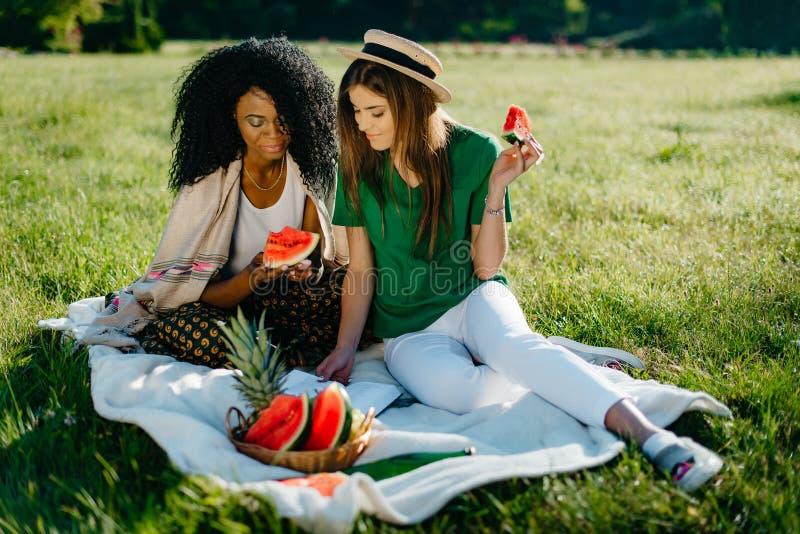 Timespending van twee multi-etnische meisjesvrienden Het vrij Afrikaanse meisje babbelt via mobiel en eet de watermeloen royalty-vrije stock fotografie