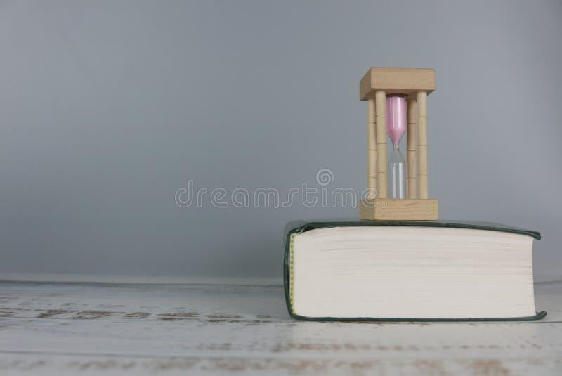 Timglas över boken tid- och utbildningsbegrepp Kopieringsutrymme f?r text eller logo arkivbild
