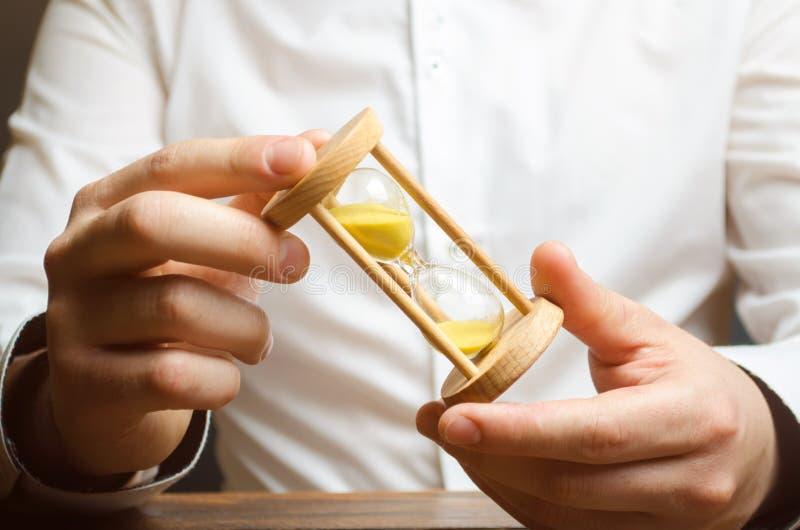 Timglas i händerna av en affärsman i en vit skjorta Planera tid och att förminska affärskostnader Fånga alla, och att göra alla p arkivfoton