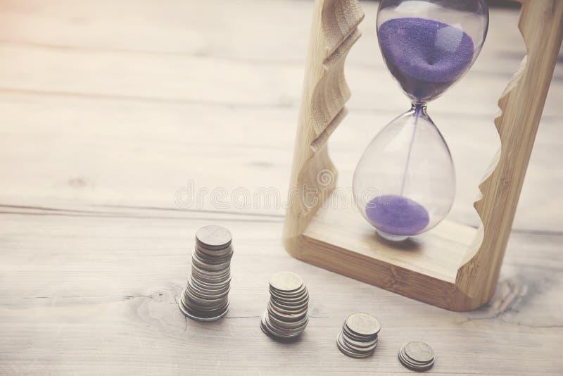 Timglas med mynt arkivbilder