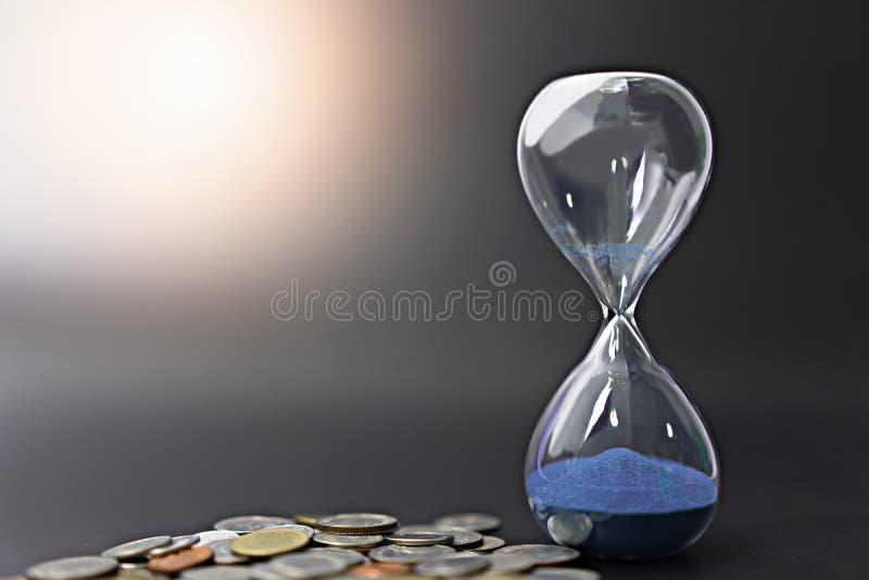 Timglas med mynt på svart bakgrund royaltyfri bild