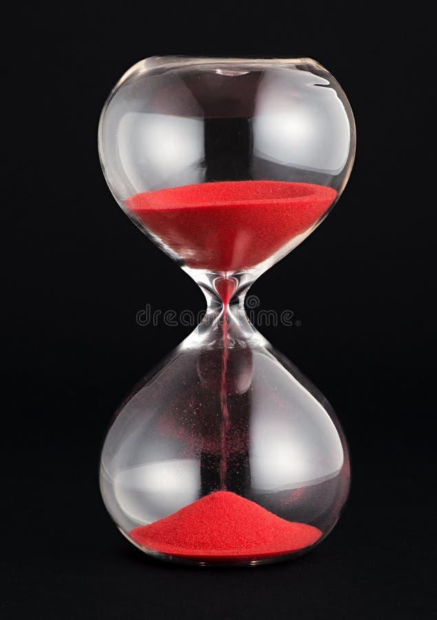 Timglas med röd sandspring till och med kulorna fotografering för bildbyråer