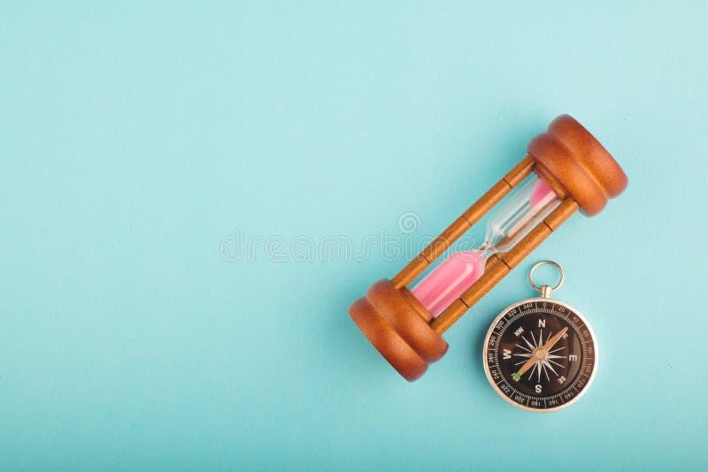 Timglas och kompass på blå bakgrund för riktning eller spring ut ur tidbegrepp royaltyfria foton