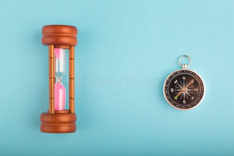 Timglas och kompass p? bl? bakgrund f?r riktning eller spring ut ur tidbegrepp arkivbild