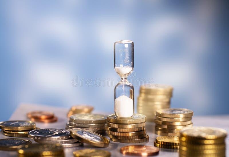 Timglas och många mynt royaltyfri bild
