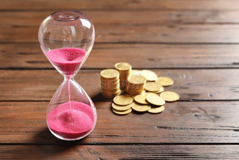Timglas och mynt på tabellen royaltyfria bilder