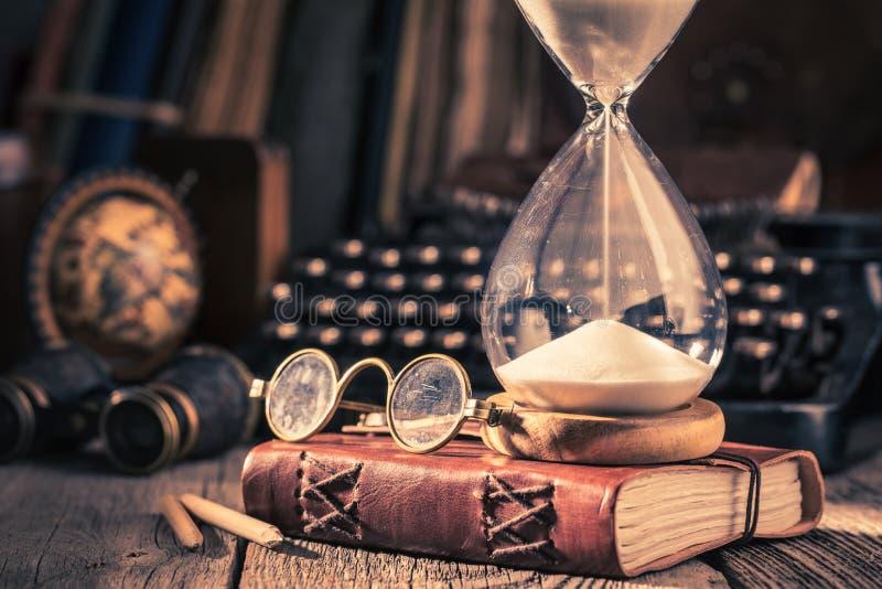 Timglas och tidskrift som minnen av gamla resor royaltyfri bild