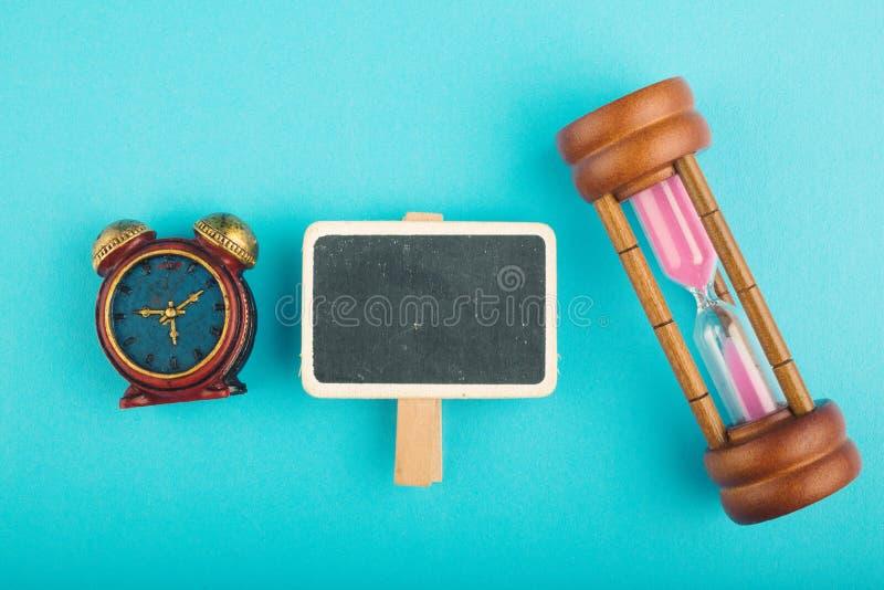 Timglas och träsignage på blå bakgrund för tidbortgångbegrepp, royaltyfri fotografi