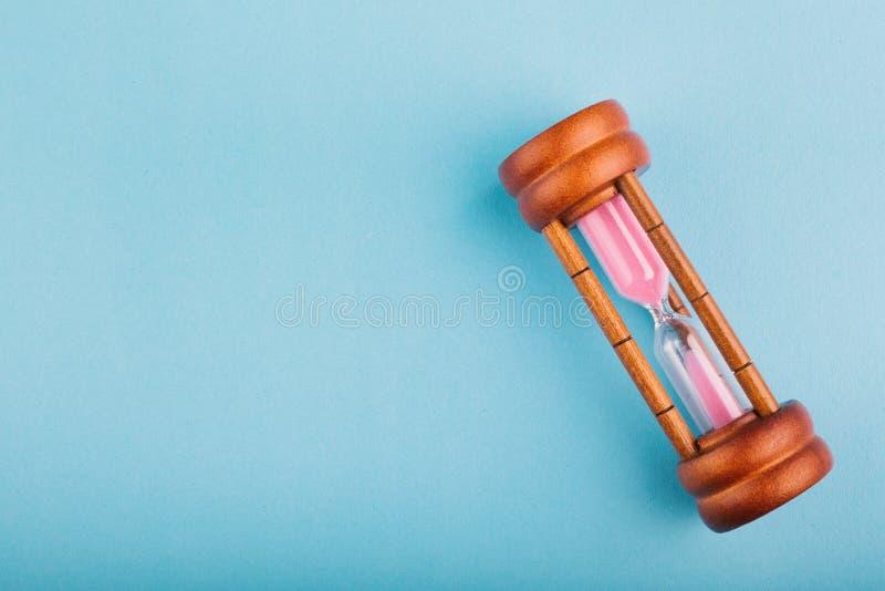 Timglas på blå bakgrund för riktning eller spring ut ur tidbegrepp, royaltyfria foton