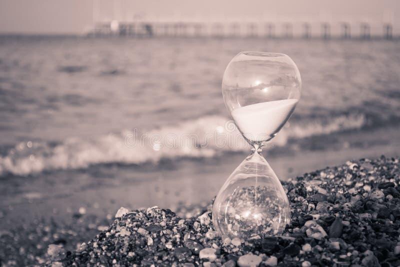 Timglas på stranden arkivbild