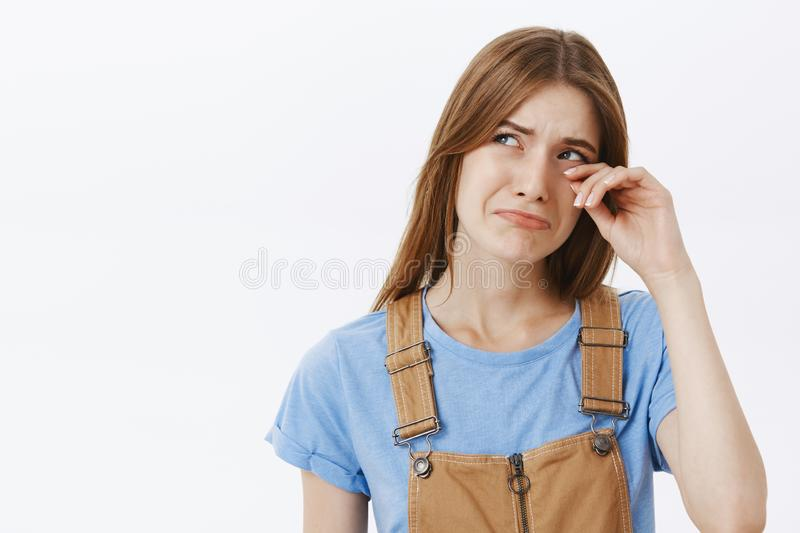 Timid silly and insecure cute european woman in blue t-shirt and overalls whining pursing lips whiping tears from ears stock image