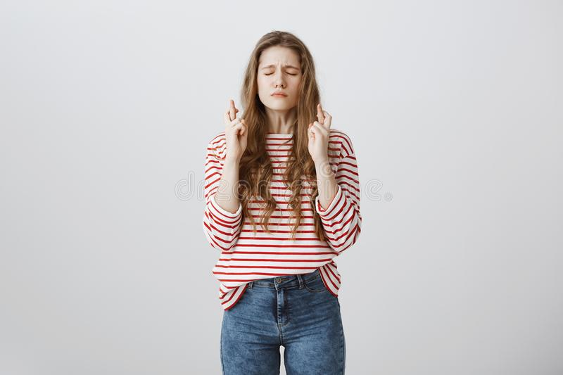 Timid and worried student praying for passing exams. Portrait of good-looking young european girl with tattoo closing stock photo