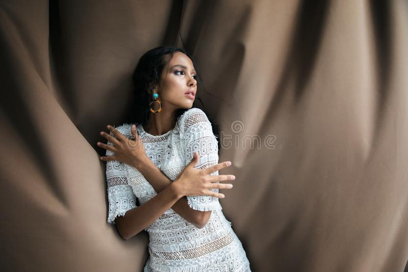 Timid Youthful Mulatto Beauty in White Lacy Dress Posing royalty free stock image