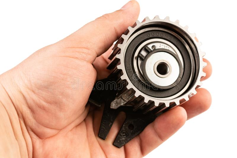 Timing belt gear wheel in the hand above white background royalty free stock images