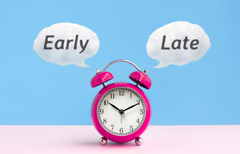 Timing and deadline concepts ideas with late,early text and cute alarm clock on pastel color. Background royalty free stock image