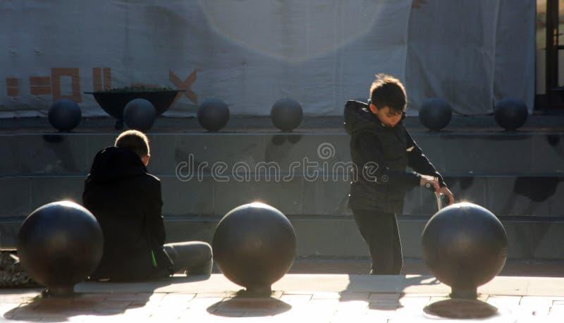 TIMISOARA, ΡΟΥΜΑΝΙΑ -12 13 2016 δύο νέα παιχνίδια αγοριών με ένα μηχανικό δίκυκλο κοντά σε μερικά σκαλοπάτια σε ένα τετράγωνο πόλ στοκ εικόνες με δικαίωμα ελεύθερης χρήσης