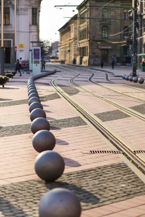 TIMISOARA - maneira do bonde do quadrado da liberdade de Piata Libertatii e bolas de metal decorativas imagem de stock