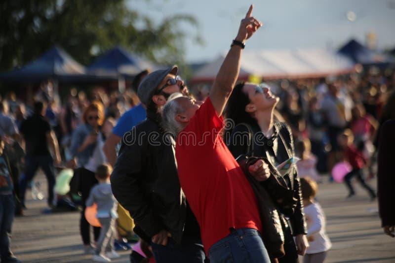 """TIMISOARA, ROEMENIË â€ """"06 23 2018 Mensen van verschillende leeftijden kijken omhoog richtend met vinger aan de vliegtuigen in de stock foto's"""
