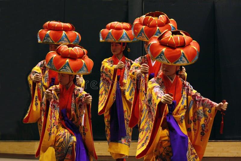 TIMISOARA, ROMANIA-11 22 2009 artistas que vestem o quimono e o chapéu tradicional do hanagasa executam uma dança de Okinawian imagem de stock