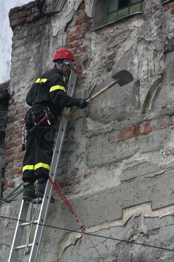 TIMISOARA, ROMANIA- 03.13.2011 A firefighter in full protective equipment climbed on a ladder removes pieces of wall that pose a d stock photos
