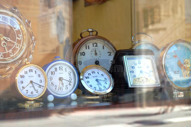 Old russian alarm clocks SLAVA and ANKER made in West Germany in a showcase of Timisoara downtown. TIMISOARA, ROMANIA - JULY 29, 2015: old russian alarm clocks royalty free stock image