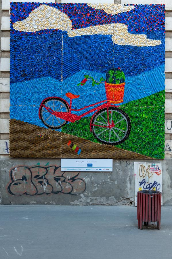 Painting made of plastic bottle caps. TIMISOARA, ROMANIA - MAY 10, 2015: Bicycle on the street, art made of multi colored bottle caps stock photography