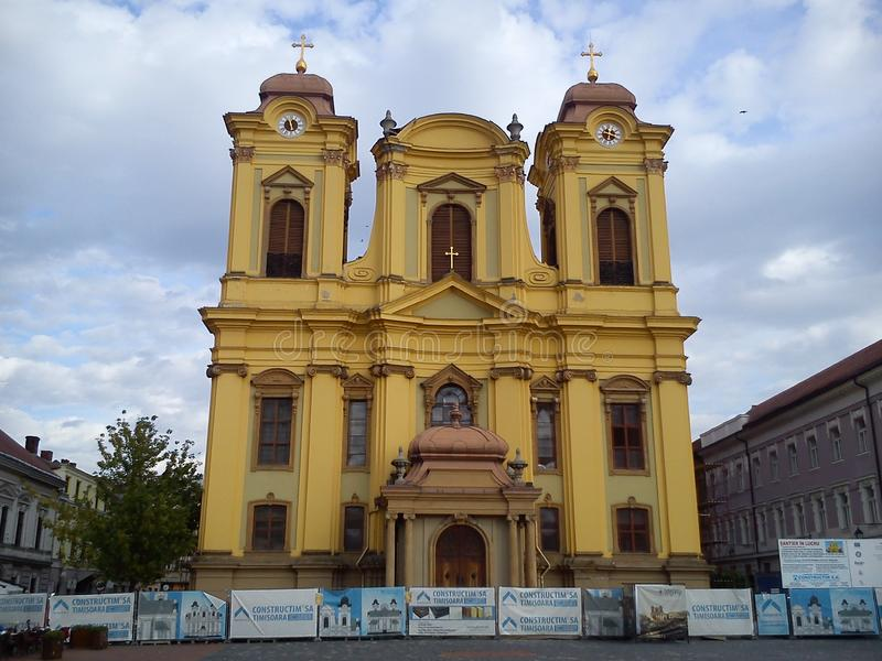 Timisoara / Romania - October 25, 2019: St. George`s Cathedral in the central square. The facade is painted in yellow paint. Sign stock images