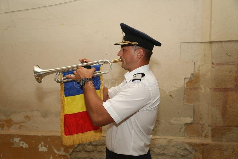 TIMISOARA, ROMANIA-08 20 Soldado 2018 novo no uniforme com tampão para jogar a trombeta com bandeira nacional uma música específi imagens de stock