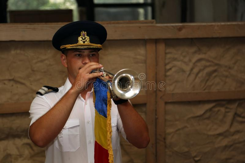 TIMISOARA, ROMANIA-08 20 Soldado 2018 novo no uniforme com tampão para jogar a trombeta com bandeira nacional uma música específi foto de stock royalty free