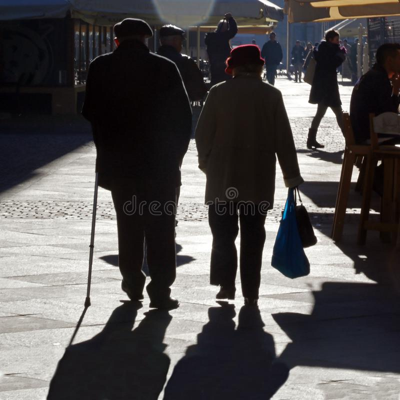 TIMISOARA RUMÄNIEN -12 13 2016 gamla par går handen - i - handen på en gata i det gamla centret in i fullt solljus arkivbild
