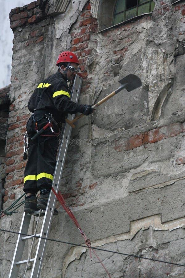 TIMISOARA, RUMANIA 03 13 2011 que un bombero en el equipo protector lleno subió en una escalera quita los pedazos de pared que pl fotos de archivo