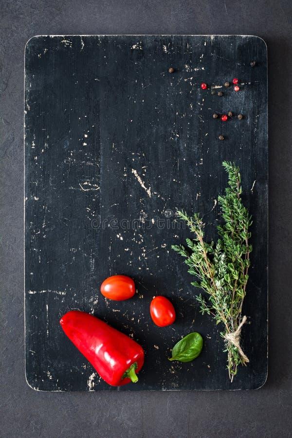 Timjan, kryddor och grönsaker på skärbräda royaltyfri fotografi