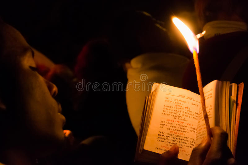 Timkat celebration in Ethiopia. Gonder, Ethiopia - January 20, 2012: priest holding a candle in the night and reading a book written in the old language of the royalty free stock image