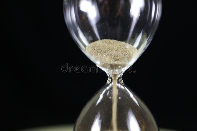 Timmeexponeringsglas - tid är pengarbegrepp arkivbilder