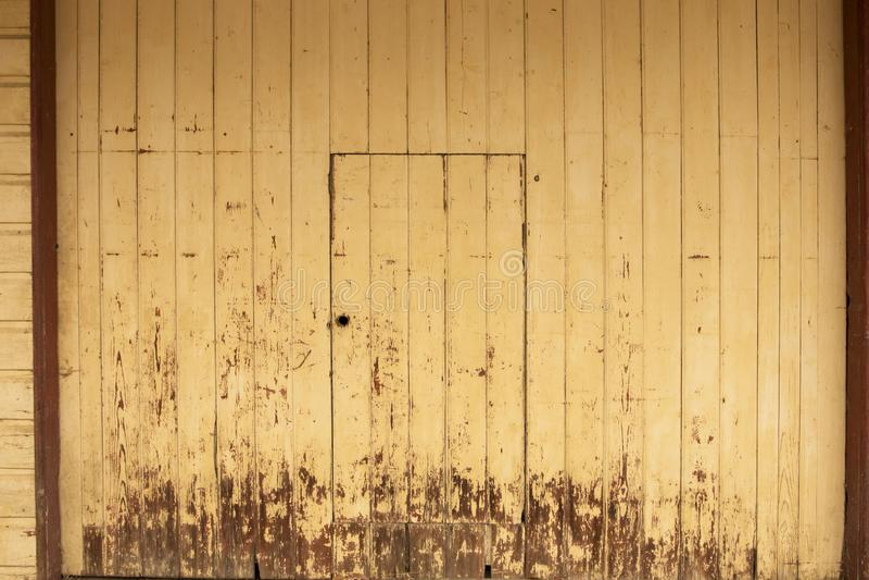 Timmerdörrbakgrund med riden ut gul målarfärg arkivfoto