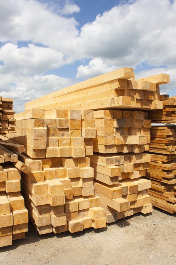Timmerhoutpakhuis in openlucht Houten die straal, planken van hout, in stapels worden gestapeld Zonnige dag, blauwe hemel met wol royalty-vrije stock afbeelding