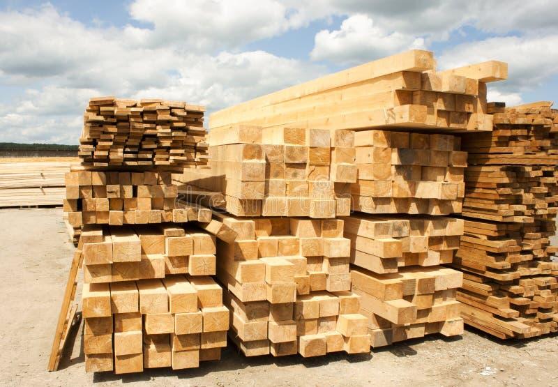 Timmerhoutpakhuis in openlucht Houten die straal, planken van hout, in stapels worden gestapeld Zonnige dag, blauwe hemel met wol royalty-vrije stock foto's