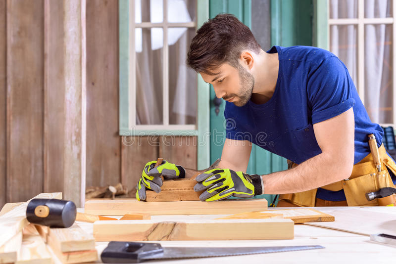 Timmerman in beschermende handschoenen die handvliegtuig voor het vormen van hout op portiek met behulp van stock afbeelding